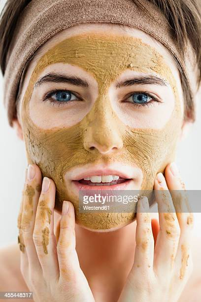 Germany, Bavaria, Munich, Portrait of young woman with clay mask, close up