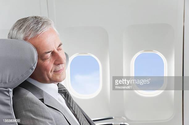 Germany, Bavaria, Munich, Senior businessman sleeping in business class airplane cabin