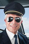 Germany, Bavaria, Munich, Senior flight captain wearing aviation glasses in airplane cockpit, smiling, close up