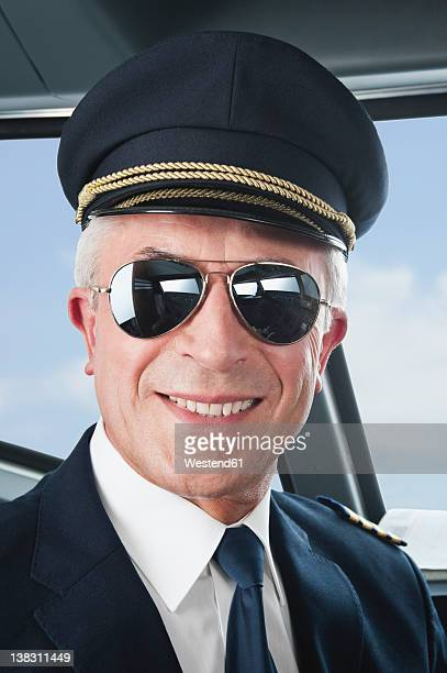 Germany, Bavaria, Munich, Senior flight captain wearing aviation glasses in airplane cockpit, smiling, close up