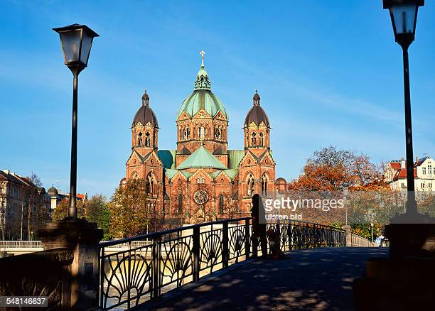 Germany Bavaria Munich Silhouette of a Woman with dog standing on Footbridge acoross the river Isar with St Lucas Church in the background