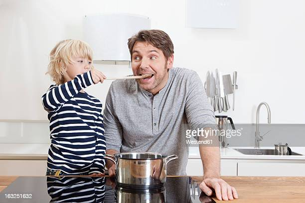 Germany, Bavaria, Munich, Son feeding father in kitchen
