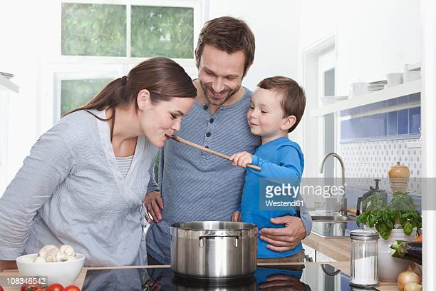 Germany, Bavaria, Munich, Son (2-3 Years) feeding mother, family in the kitchen