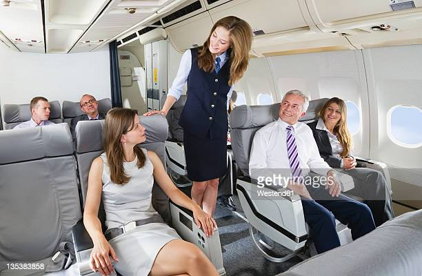 Germany, Bavaria, Munich, Stewardess and passengers in business class airplane cabin, smiling