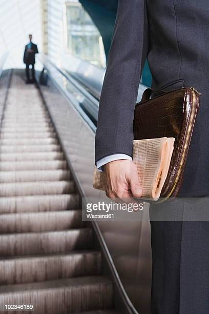 Germany, Bavaria, Munich, Businessman on escalator holding briefcase, mid section, close-up