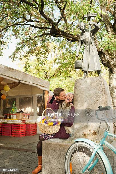 Germany, Bavaria, Munich, Viktualienmarkt, Couple by fountain holding basket with flowers, portrait