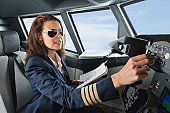 Germany, Bavaria, Munich, Woman flight captain with map in airplane cockpit