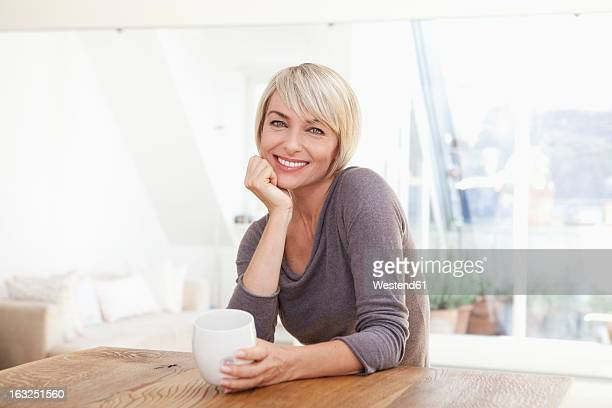 Germany, Bavaria, Munich, Woman holding cup at table, smiling, portrait
