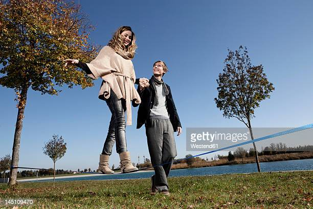 Germany, Bavaria, Munich, Woman on slackline with man, smiling