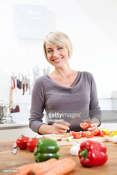 Germany, Bavaria, Munich, Woman preparing food in kitchen