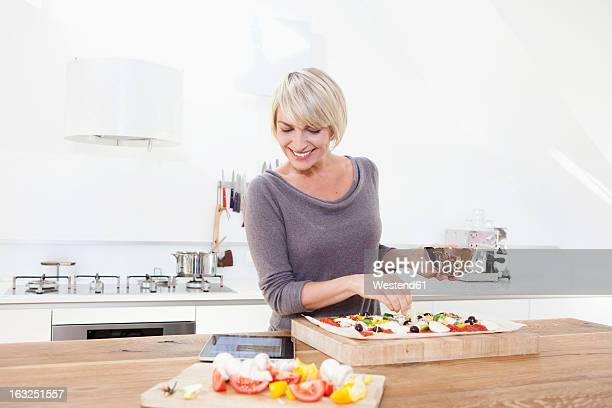 Germany, Bavaria, Munich, Woman preparing pizza in kitchen