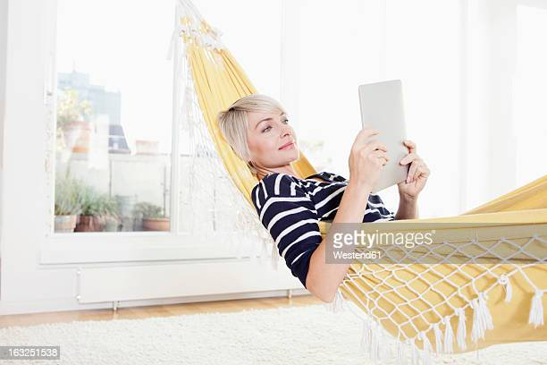 Germany, Bavaria, Munich, Woman relaxing in hammock and watching digital tablet