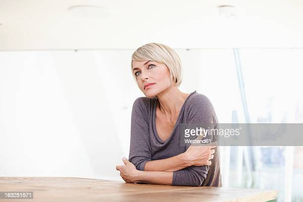 Germany, Bavaria, Munich, Woman thinking at table