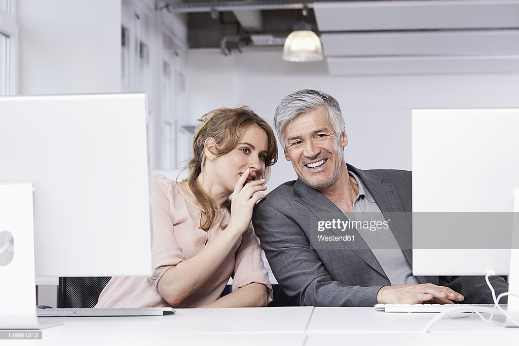 Germany, Bavaria, Munich, Woman whispering in man's ear in office