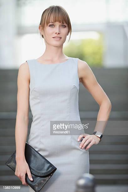 Germany, Bavaria, Munich, Young businesswoman holding purse, smiling, portrait