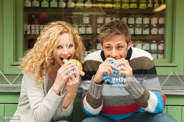 Germany, Bavaria, Munich, Young couple at Viktualienmarkt having snack, portrait