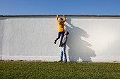 Germany, Bavaria, Munich, Young couple climbing wall