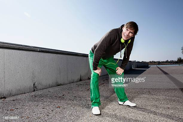 Germany, Bavaria, Munich, Young man resting after exercising