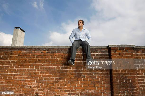 Germany, Bavaria, Munich, Young man sitting on wall, low angle view