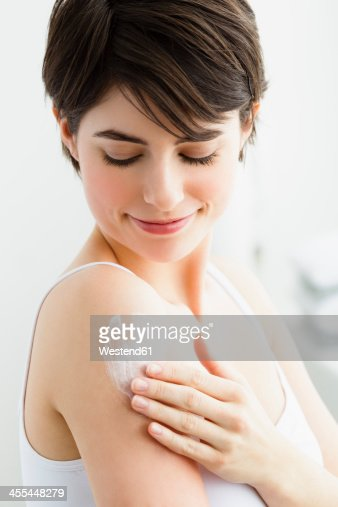 Germany, Bavaria, Munich, Young woman applying cream on hand, smiling