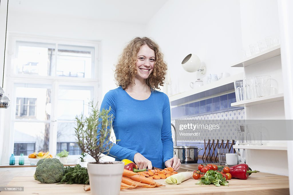 Germany, Bavaria, Munich, Young woman chopping vegetables in kitchen, smiling, portrait : Stock Photo