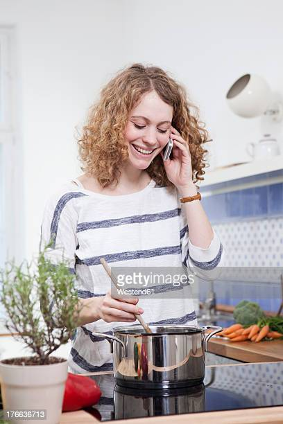Germany, Bavaria, Munich, Young woman cooking and talking on phone in kitchen, smiling