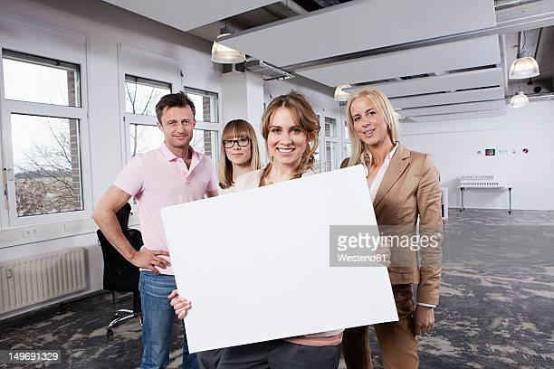 Germany, Bavaria, Munich, Young woman holding placard with colleagues in office