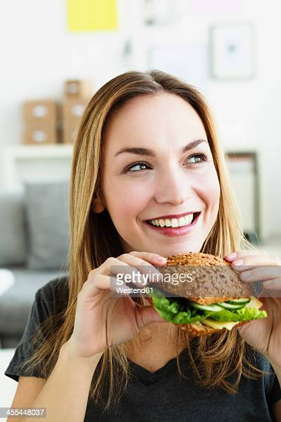 Germany, Bavaria, Munich, Young woman holding sandwich, looking away