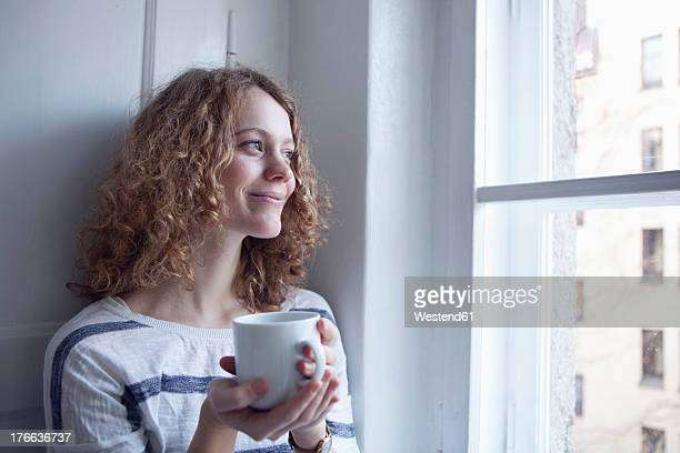 Germany, Bavaria, Munich, Young woman looking out of window, smiling