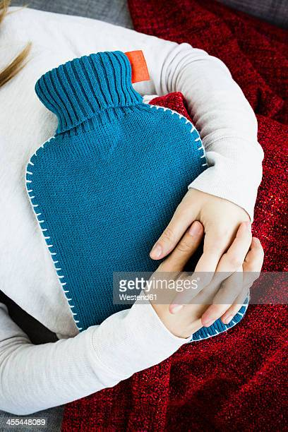 Germany, Bavaria, Munich, Young woman lying on couch with hot water bottle, close up