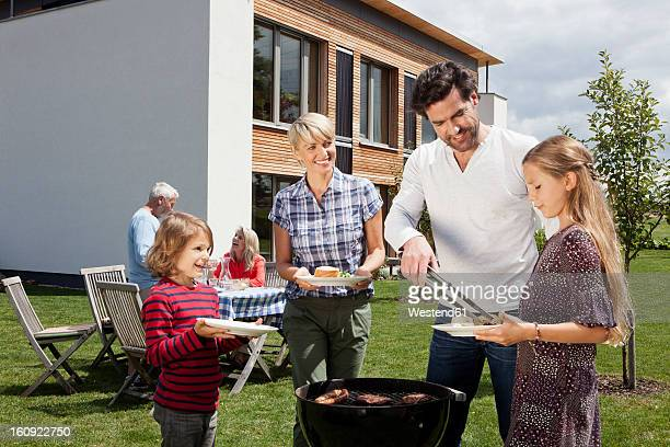 Germany, Bavaria, Nuremberg, Family barbucue in garden