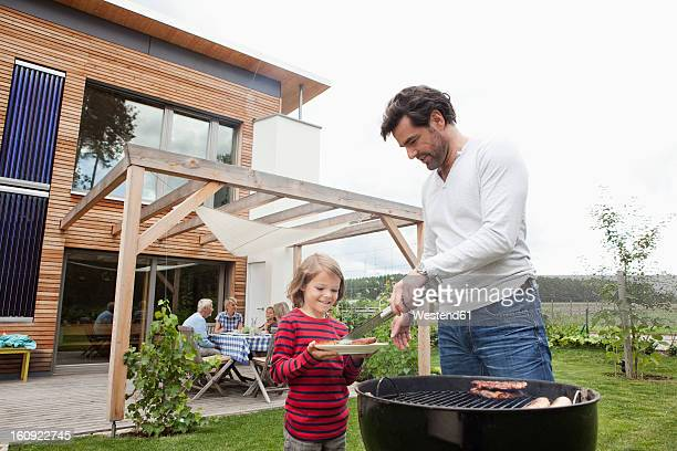 Germany, Bavaria, Nuremberg, Father and son preparing food on barbecue, family sitting in background