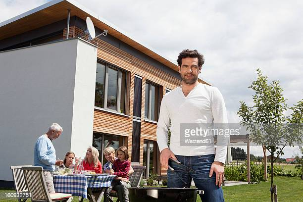 Germany, Bavaria, Nuremberg, Man cooking barbecue, family sitting in garden