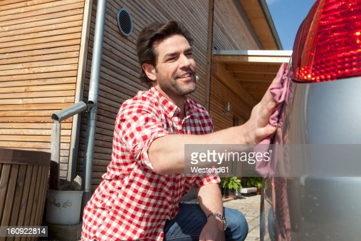 Germany, Bavaria, Nuremberg, Mature man cleaning car in front of house