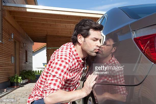 Germany, Bavaria, Nuremberg, Mature man kissing car