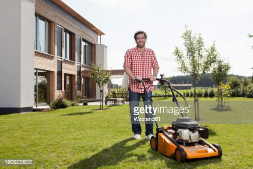 Germany, Bavaria, Nuremberg, Mature man with lawn mower in garden