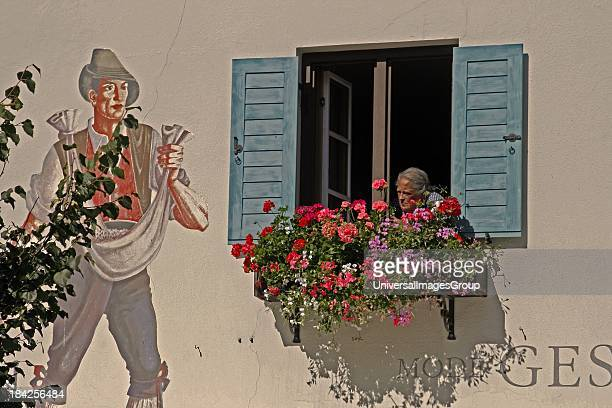 Germany Bavaria Oberammergau Painted building facade with windows and shutters luftmaileri elderly woman in window