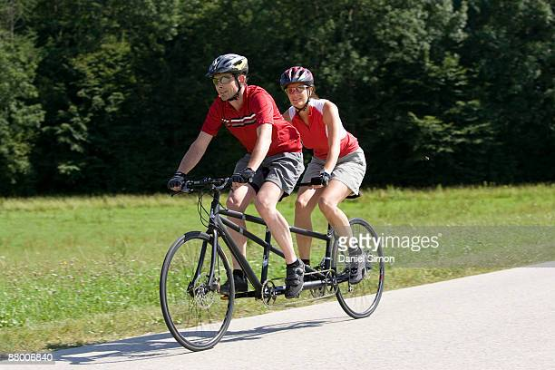 Germany, Bavaria, Oberland, couple riding tandem bicycle