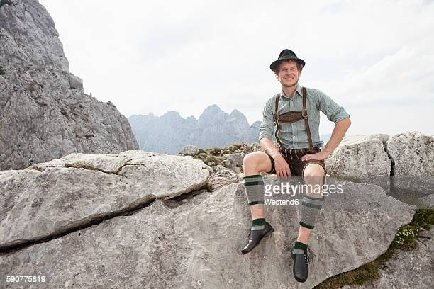 Germany, Bavaria, Osterfelderkopf, man in traditional clothes sitting in mountain landscape