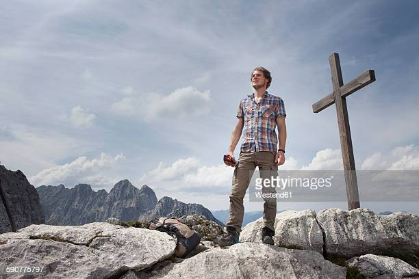 Germany, Bavaria, Osterfelderkopf, man standing at summit cross