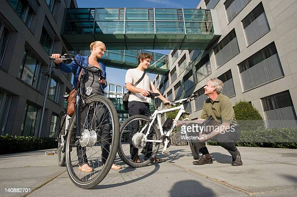 Germany, Bavaria, People with cycle discussing together, smiling