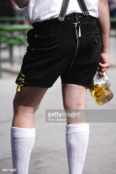 Germany, Bavaria, Man in traditional costume holding beer glass, rear view, mid section
