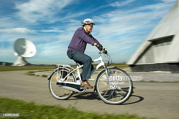 Germany, Bavaria, Raisting, Man riding electric bicycle near radio station