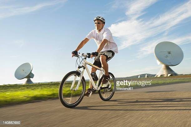 Germany, Bavaria, Raisting, Man riding electric bicycle near radio station