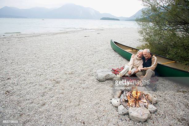 Germany, Bavaria, Walchensee, Senior couple sitting at campfire, elevated view