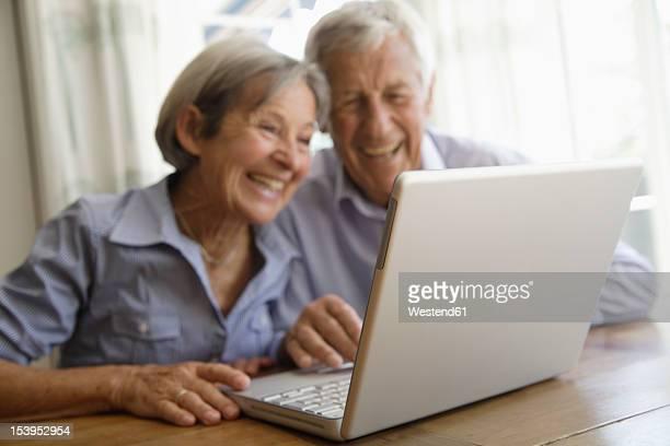 Germany, Bavaria, Senior couple using laptop at home, smiling