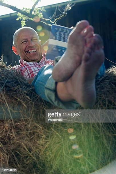Germany, Bavaria, Mature man sitting on haystack reading book, smiling