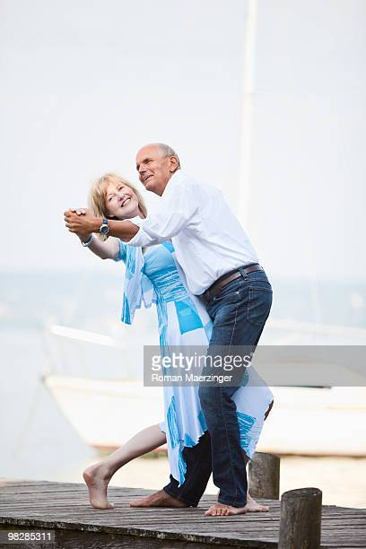 Germany, Bavaria, Starnberger See, Couple dancing on jetty, smiling