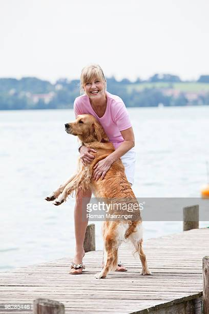 Germany, Bavaria, Starnberger See, Mature woman with golden retriever on jetty, smiling