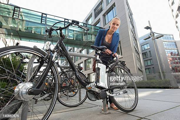Germany, Bavaria, Teenage girl fixing lock of bicycle